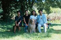 犬(ゴールデンレトリバー)を連れた日本人の4人家族