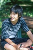 携帯電話を持つ木陰の日本人男の子