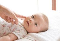 赤ちゃんとほっぺを触る母親の手