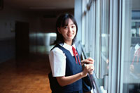 廊下に立つ制服を着た日本人の女の子