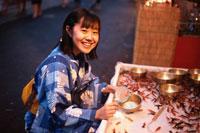 浴衣を着て金魚すくいをしている日本人女性