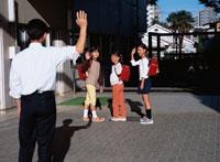 女子学生3人の下校を見送る男性教師