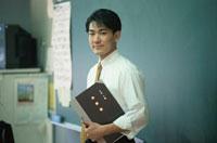 出席簿を持って立っている男性教師