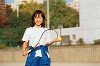 校庭でテニスラケットを持つ日本人の女子学生