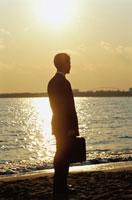 夕日を眺めているビジネスマンのシルエット