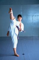 足を蹴り上げる空手の胴衣を着た日本人女子高生