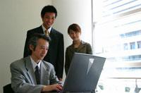 パソコンに向かう3人の日本人ビジネスマンとビジネスウーマン