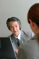 部下の女性と向き合う日本人ビジネスマン