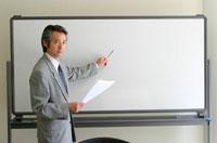 ホワイトボードで説明する日本人ビジネスマン