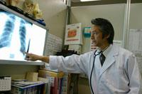 レントゲン写真を指差す日本人医師