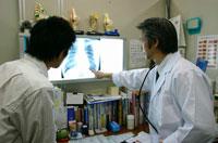 男性患者にレントゲン写真の説明をする日本人医師