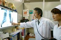 看護婦にレントゲン写真の説明をする日本人医師
