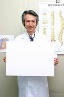 メッセージボードを持つ日本人医師