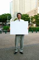 メッセージボードを持つ日本人ビジネスマン