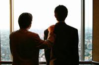 窓辺に立つ2人の日本人ビジネスマン