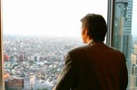 窓越しに外を眺める日本人ビジネスマン