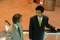 エスカレーターに乗る2人の日本人ビジネスマン