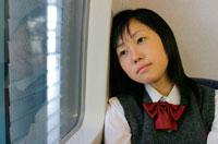 電車内で窓辺にもたれかかる日本人の女子学生