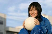 バレーボールを抱えるジャージ姿の日本人の女子学生