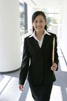 笑顔で廊下を歩く日本人ビジネスウーマン