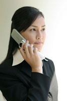 携帯電話をかける日本人ビジネスウーマン