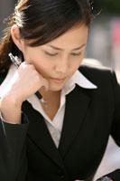 ペンを握り頬杖をつく日本人ビジネスウーマン