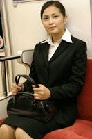 電車の座席に座る日本人ビジネスウーマン