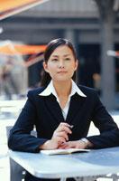 屋外で手帳を開きペンを持つ日本人ビジネスウーマン