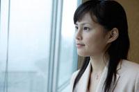 窓辺に立つスーツ姿の日本人女性