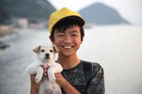 海辺で子犬を抱く小学生の男子 02208001141A| 写真素材・ストックフォト・画像・イラスト素材|アマナイメージズ
