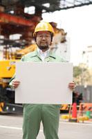 建設現場で白い紙を持つ作業着の男性