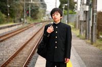 駅のホームに立つ男子中学生