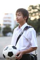 サッカーボールを持った制服姿の中学生男子