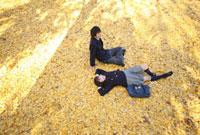 イチョウの絨毯の上の高校生カップル