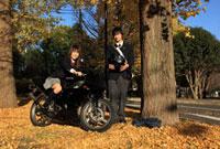 イチョウの木の下でバイクに跨る女子高生と男子高生