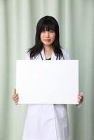 メッセージボードを持つ日本人女医