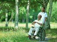 車椅子の父と散歩する娘