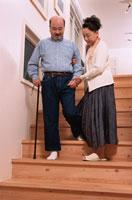 階段を支えて下りる日本人の中高年夫婦 02234000099  写真素材・ストックフォト・画像・イラスト素材 アマナイメージズ