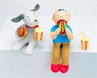 ホットドッグを食べる男性と犬