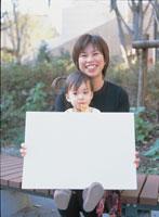 メッセージボードを持つ母子