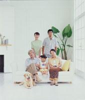 リビングのソファに集まる三世代家族と犬