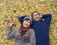 落ち葉に寝そべる夫婦
