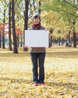 公園でホワイトボードを持つ女性 02253004560| 写真素材・ストックフォト・画像・イラスト素材|アマナイメージズ