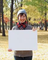 公園でホワイトボードを持つ女性