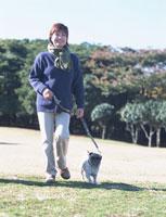 公園で犬を散歩させるシニア女性 02253005112| 写真素材・ストックフォト・画像・イラスト素材|アマナイメージズ