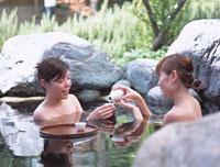 露天風呂に入りお酒を飲む女性2人