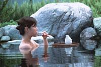 露天風呂に入りお酒を飲む女性