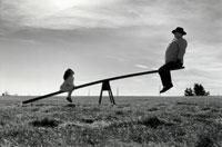 シーソーに乗る少女と大男