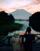 山と湖を眺める人物2人の後ろ姿 02265008238| 写真素材・ストックフォト・画像・イラスト素材|アマナイメージズ