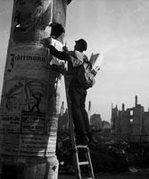 柱にはしごで張り紙をする男性 ベルリン ドイツ 1946年